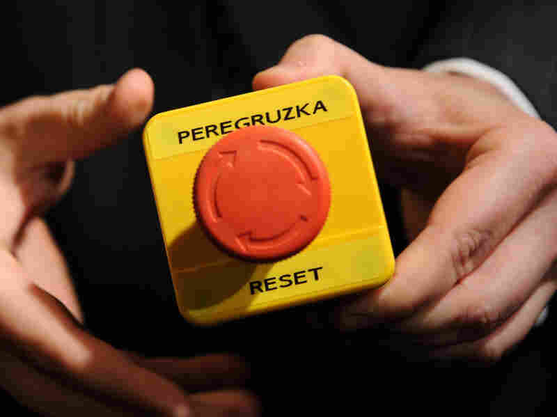"""An assistant shows the block with a red button marked """"reset"""" in English and """"overload"""" in Russian that U.S. Secretary of State Hillary Clinton handed to Russian Foreign Minister Sergei Lavrov during a 2009 meeting in Geneva."""