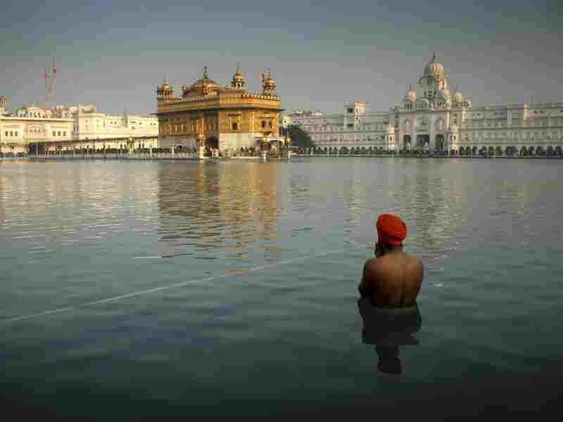 A Sikh devotee takes a holy dip in the sacred pond at the Golden Temple in Amritsar, India, on Jan. 1. Official British documents released Tuesday suggest the U.K. helped India plan the deadly 1984 raid on the shrine where militants h