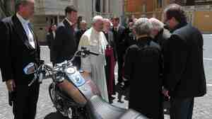 Pope Francis stands by a Harley-Davidson he was given, at the Vatican in June. The bike is to be sold at auction to raise money for charity.