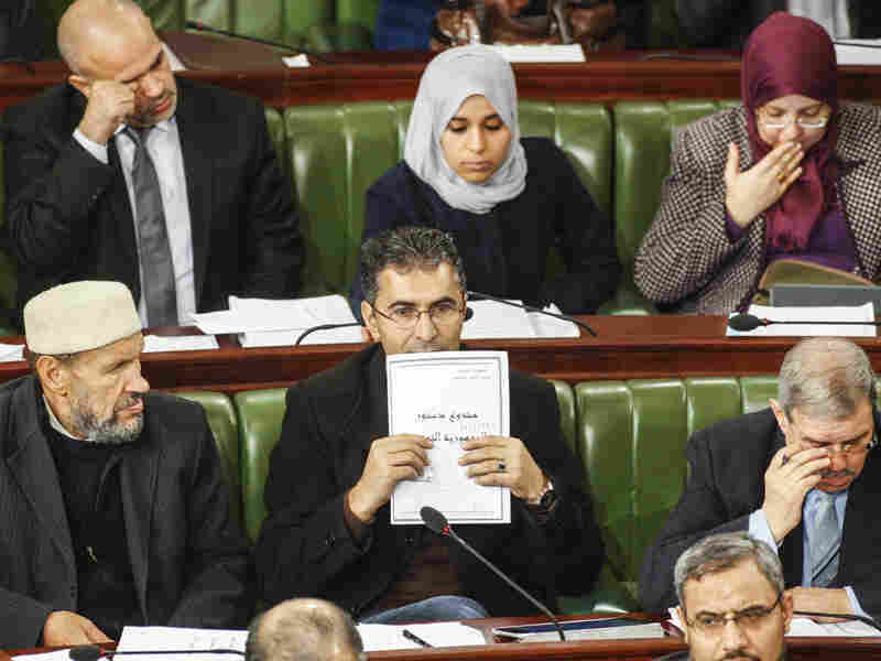 Parliament member Moez Belhaj Rhouma holds a copy of Tunisia's draft constitution, on Jan. 3 in Tunis. Lawmakers spent two years writing the new constitution, which is expected to receive final approval this week.