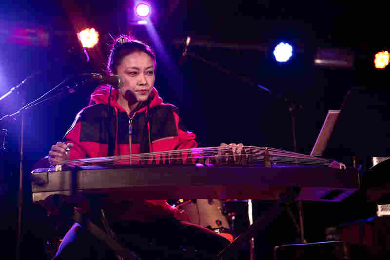 Chinese artist Wu Fei sings and plays the guzheng, a traditional zither, in the trio.