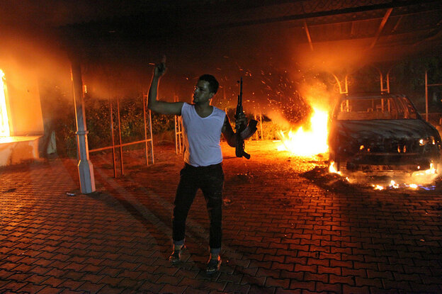 An armed man waves his arms as buildings and cars are engulfed in flames after being set on
