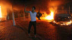 An armed man waves his arms as buildings and cars are engulfed in flames after being set on fire inside the U.S. Consulate compound in Benghazi late on Sept. 11, 2012.