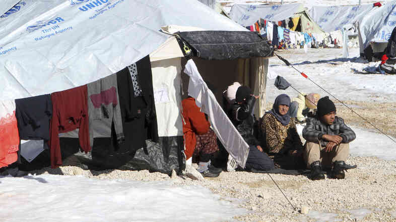 Syrian refugees sit by their tent in a camp on the Lebanese border town of Arsal on Dec. 15.