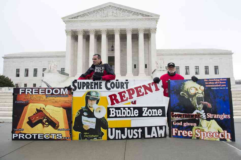 Pro-life demonstrators stand outside the U.S. Supreme Court following oral arguments in the case dealing with a Massachusetts law imposing a 35-foot buf
