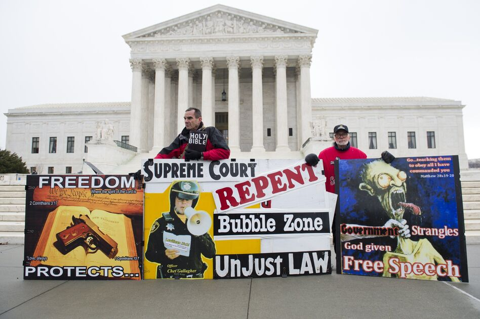 Pro-life demonstrators stand outside the U.S. Supreme Court following oral arguments in the case dealing with a Massachusetts law imposing a 35-foot buffer zone around abortion clinics for demonstrations and protests. (Saul Loeb/AFP/Getty Images)