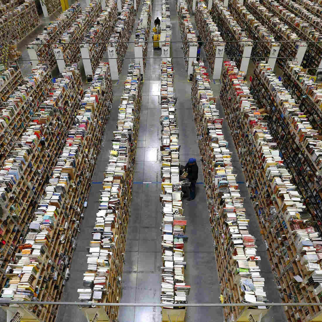 An Amazon.com employee stocks products along one of the many miles of aisles at an Amazon.com Fulfillment Center in Phoenix last month.