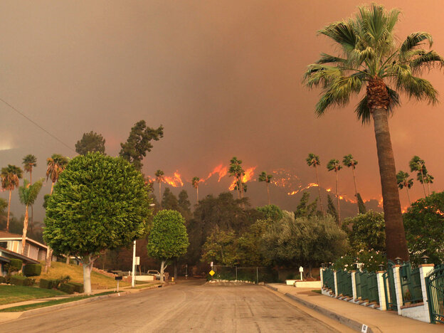 A wildfire burns in the hills just north of