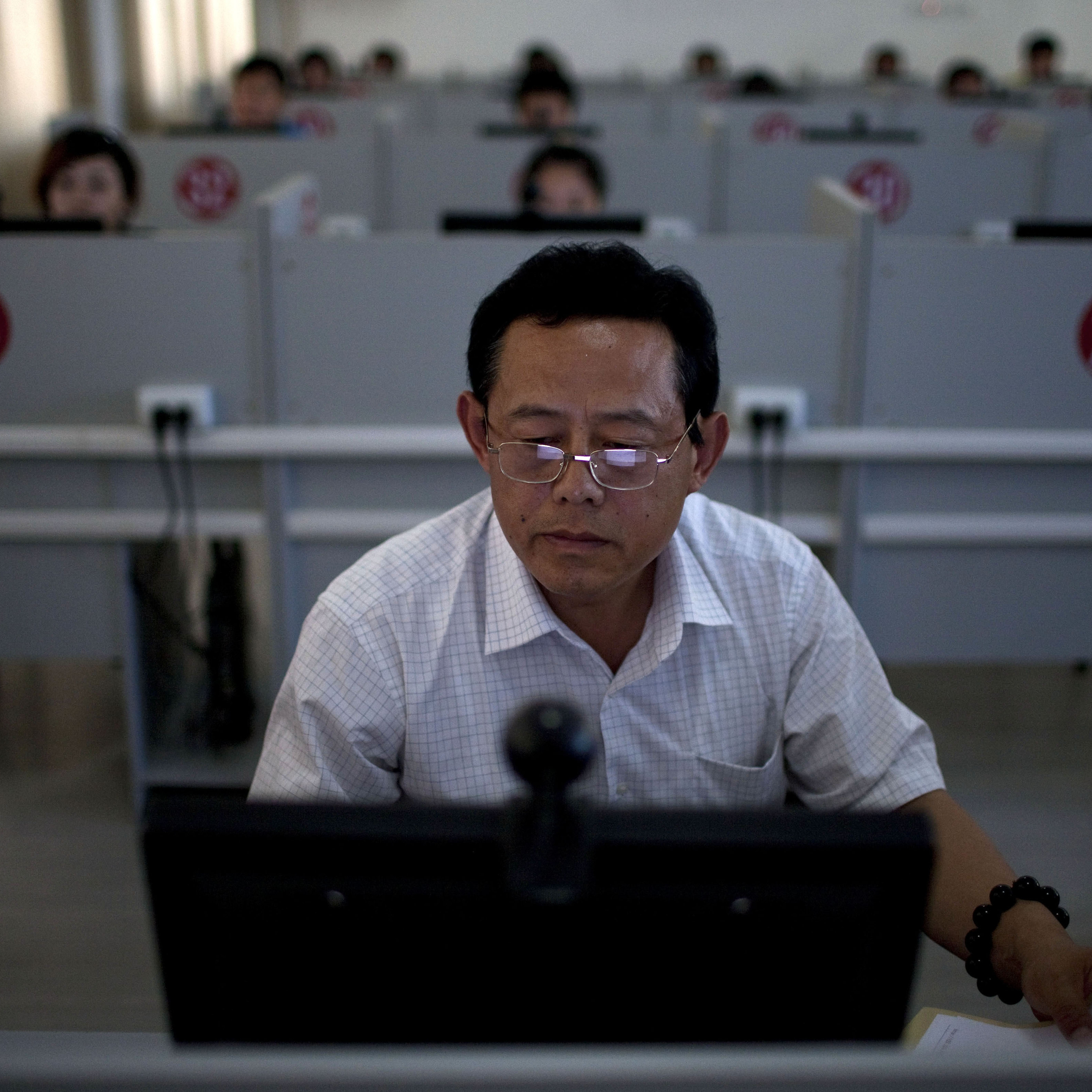 A man takes a computerized road rules test at a driving school in Jinan, in eastern China's Shandong province, in 2011. Most Chinese people -- accustomed to an education system that emphasizes rote memorization -- don't find the test as difficult as foreigners.