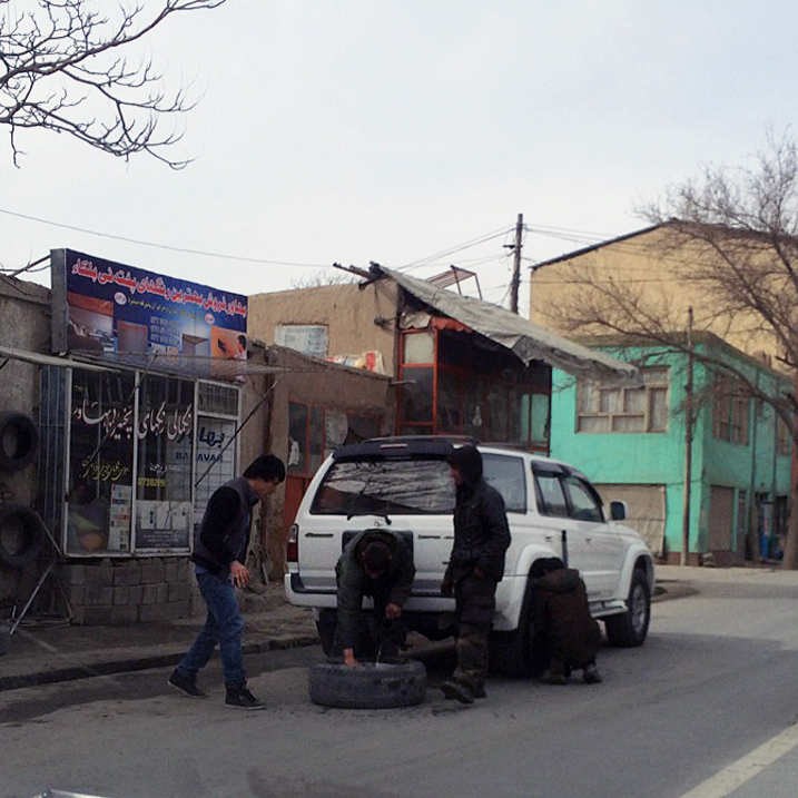 Afghans change a tire on the side of a street in Kabul's 10th District, where police have been puncturing tires at night to prevent car theft.