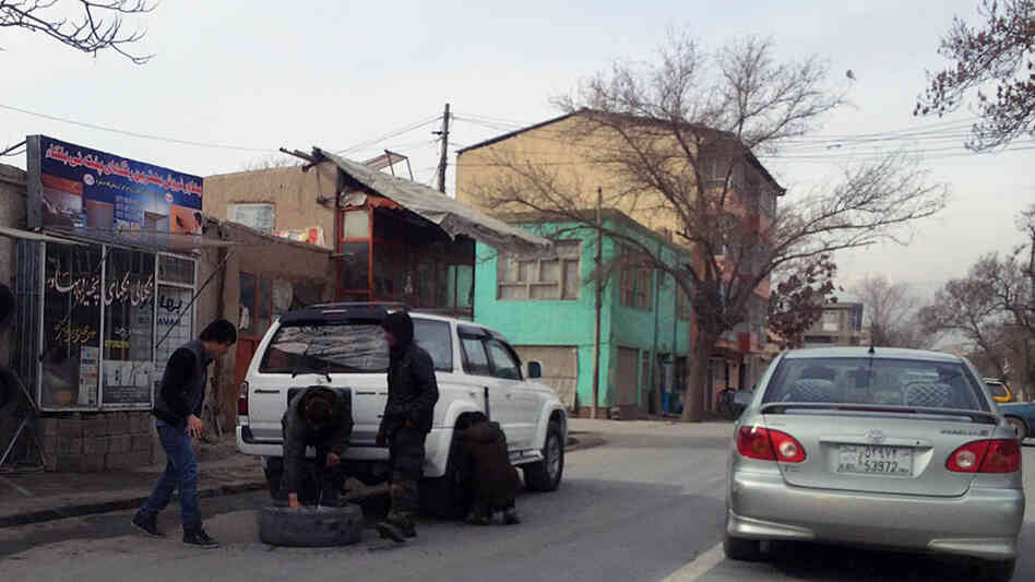 Afghans change a tire on the side of a street in Kabul's 10th District, where police