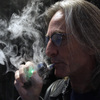 John Hartigan, proprietor of Vapeology LA, a store selling electronic cigarettes and related items, takes a puff from an electronic cigarette in Los Angeles.