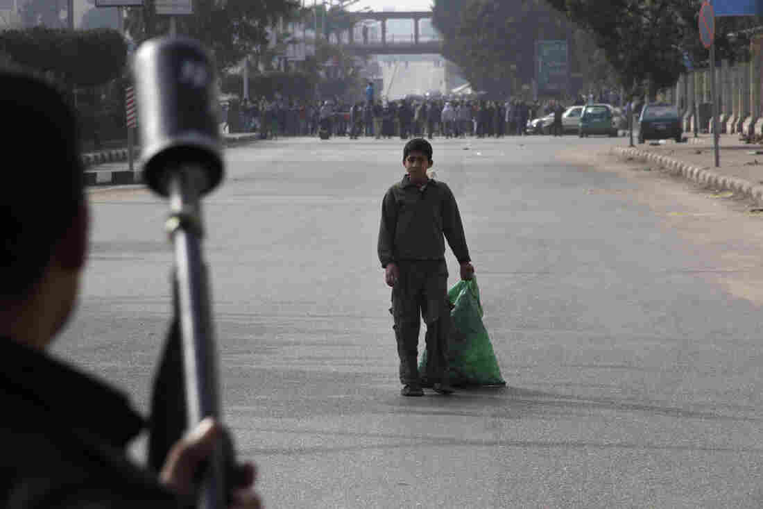 A boy looks at Egypt's security forces as they try to disperse supporters of ousted President Mohammed Morsi in Cairo on Friday.