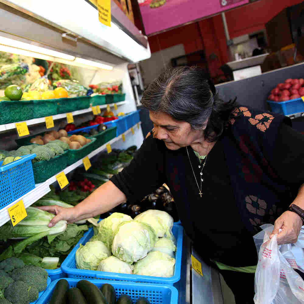 A customer buys produce at the Euclid Market in the Boyle Heights neighborhood of East Los Angeles in December. The market was reopened in 2013 as part of a project to promote healthy eating among the city's Hispanic population.