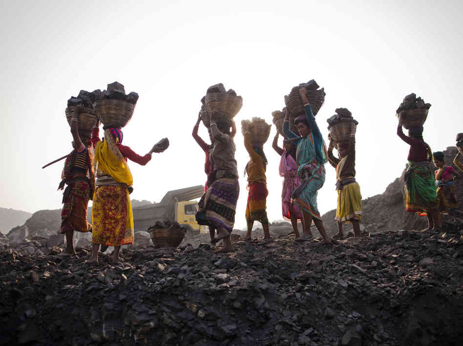 Local villagers scavenging  coal illegally from an open-cast mine in a village near Jharia, India,