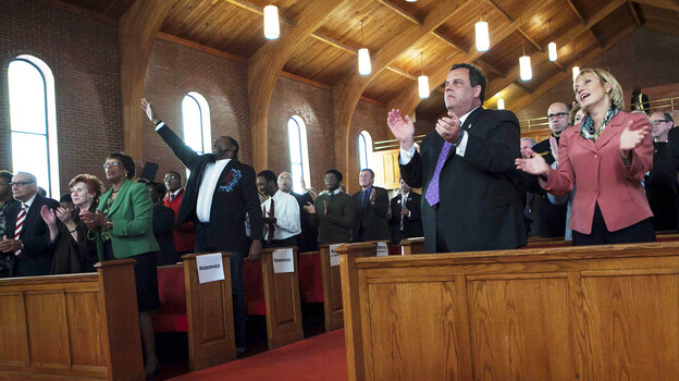 New Jersey Gov. Chris Christie joins Lt. Gov. and Secretary of State Kim Guadagno (right) at a statewide prayer service in Newark marking the one-year anniversary of Superstorm Sandy, in October. (AP)