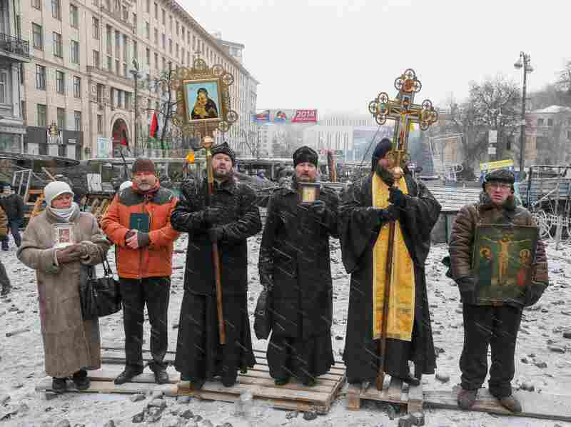 Ukrainian priests stand between protesters and riot police during an anti-government protest Monday in Kiev.