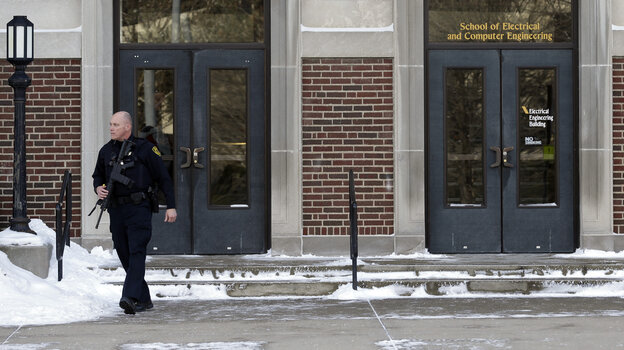 A police officer walks out of the Electrical Engineering Building on