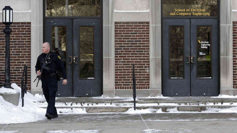 A police officer walks out of the Electrical Engineering Building on the campus of Purdue University in West Lafayette, Ind., Tuesday. One person was killed in a classroom by a gunman who surrendered to a police officer within minutes of the attack, officials sai