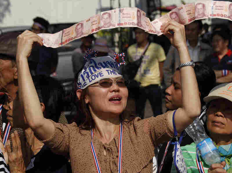 An anti-government supporter displays her donations for the cause during a street rally in Bangkok, Thailand, on Tuesday. Thailand has declared a state of emergency in Bangkok and its surrounding areas to cope with anti-government protests that have stirred up violent attacks.