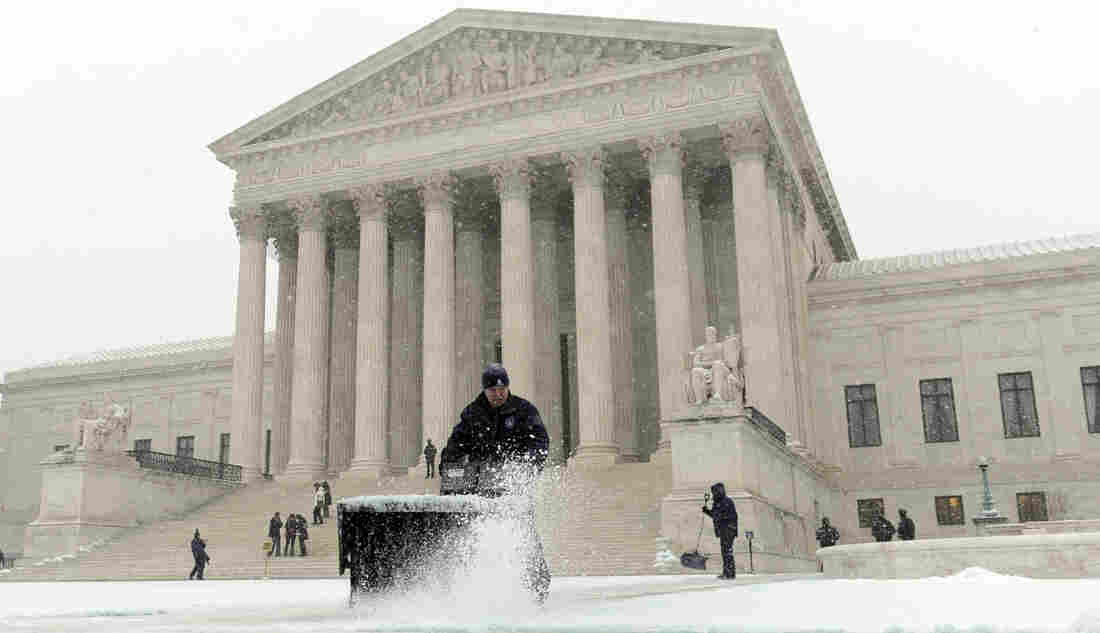 A worker clears snow from in front of the U.S. Supreme Court in Washington, D.C., on Tuesday.