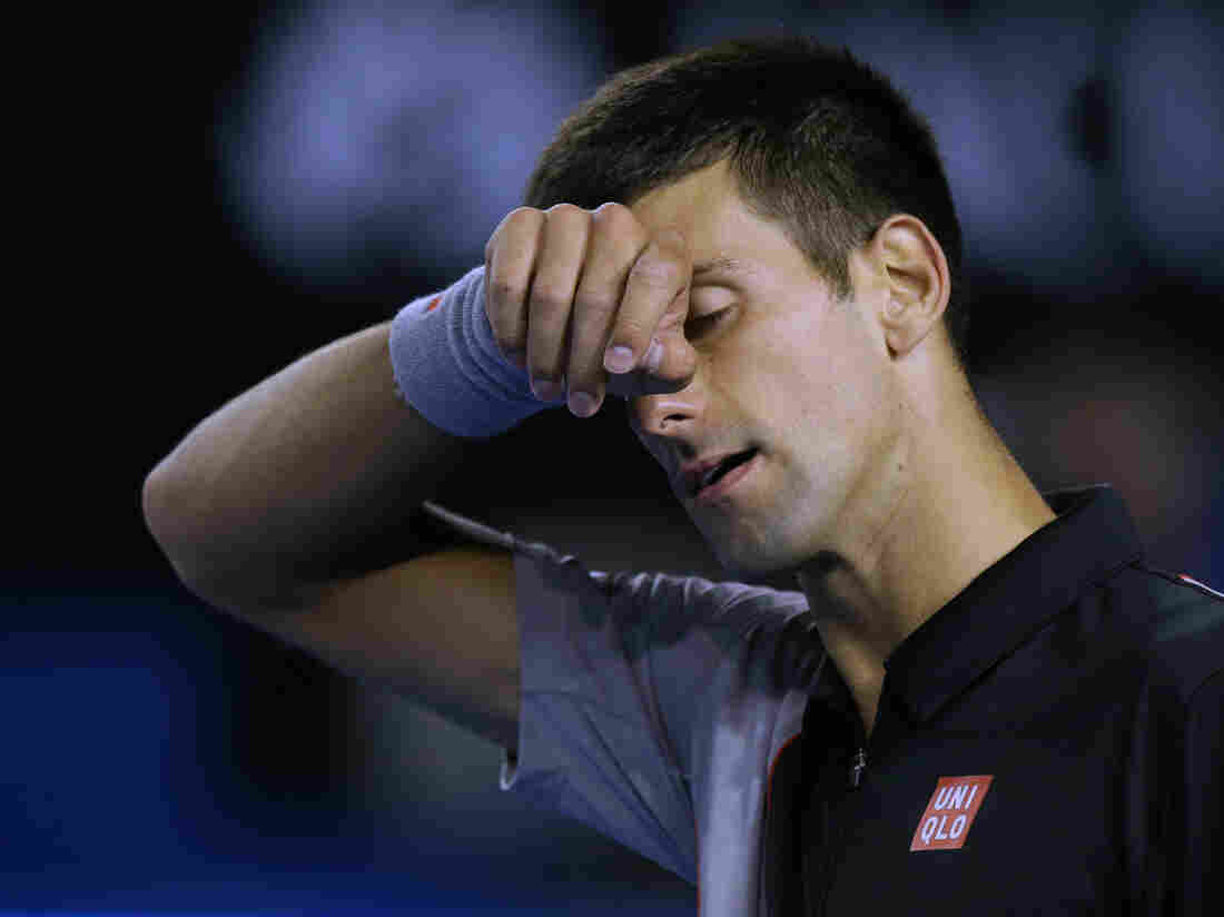 Novak Djokovic of Serbia wipes the sweat from his face during his quarterfinal loss to Stanislas Wawrinka of Switzerland at the Australian Open tennis championship in Melbourne.