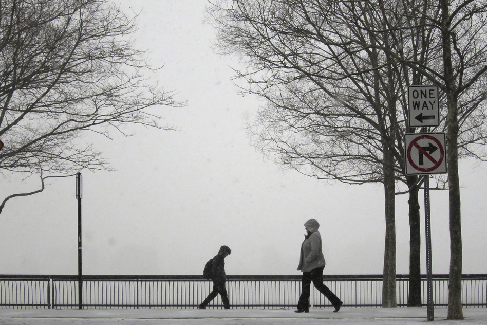 People walk in a park along the Hudson River across from New York City as snow begins to fall in Hoboken. (Reuters/Landov)