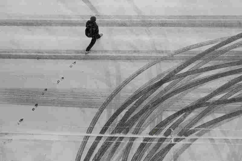 A man crosses the street as snow falls in Baltimore.