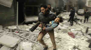 A man runs with a child after an attack Tuesday in the northern Syrian city of Aleppo. Activists said President Bashar Assad's military carried out an airstrike.