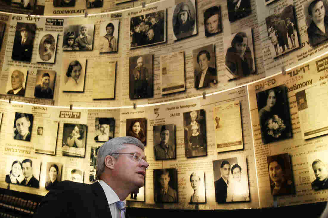 Canadian Prime Minister Stephen Harper looks at pictures of Jewish Holocaust victims at the Hall of Names while visiting Yad Vashem on Tuesday.