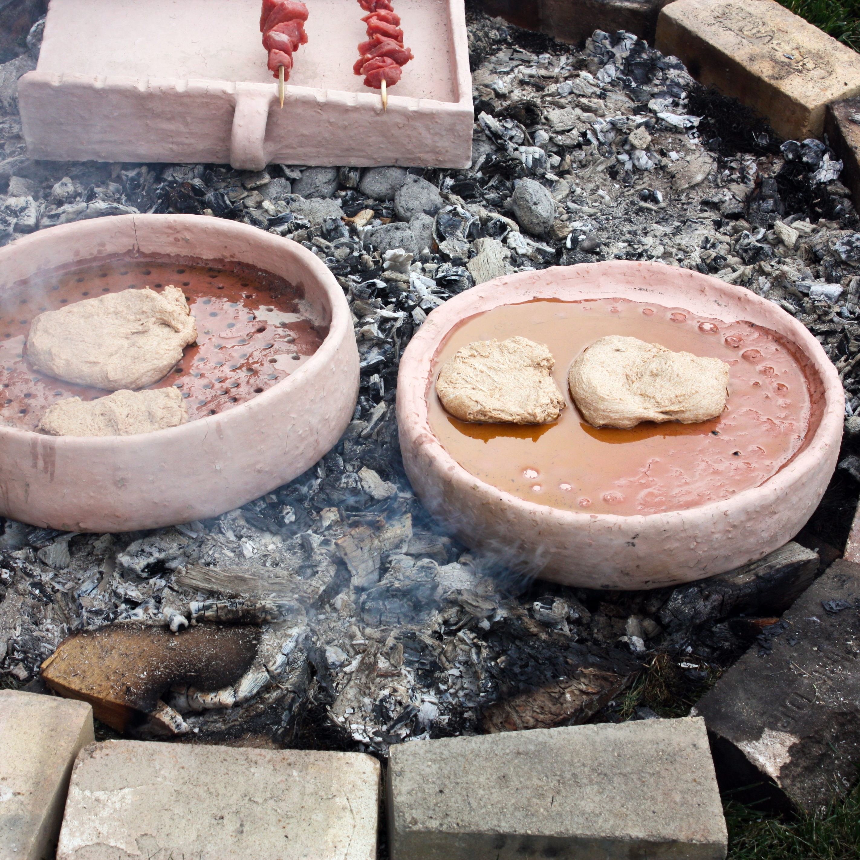A replica of a perforated griddle is filled with dough to demonstrate how the ancient Greeks made bread.
