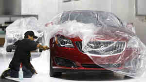 Auto show worker Jorge Martinez details a 2014 Buick Regal in preparation for display Jan. 11. The Regal is equipped with technology that senses a potential accident and slows the car automatically.