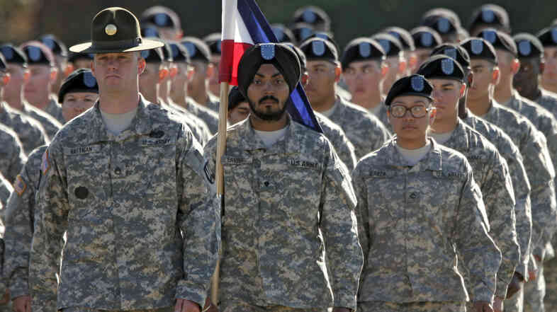 U.S. Army Spc. Simran Lamba (center) was granted a religious accommodation for his Sikh articles of faith, including uncut hair and a turban, in 2010. He was the first enlisted soldier to be given such an accommodation since 1984.