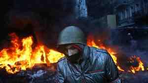 A protester walks pass burning tires in central Kiev, Ukraine, on Thursday.