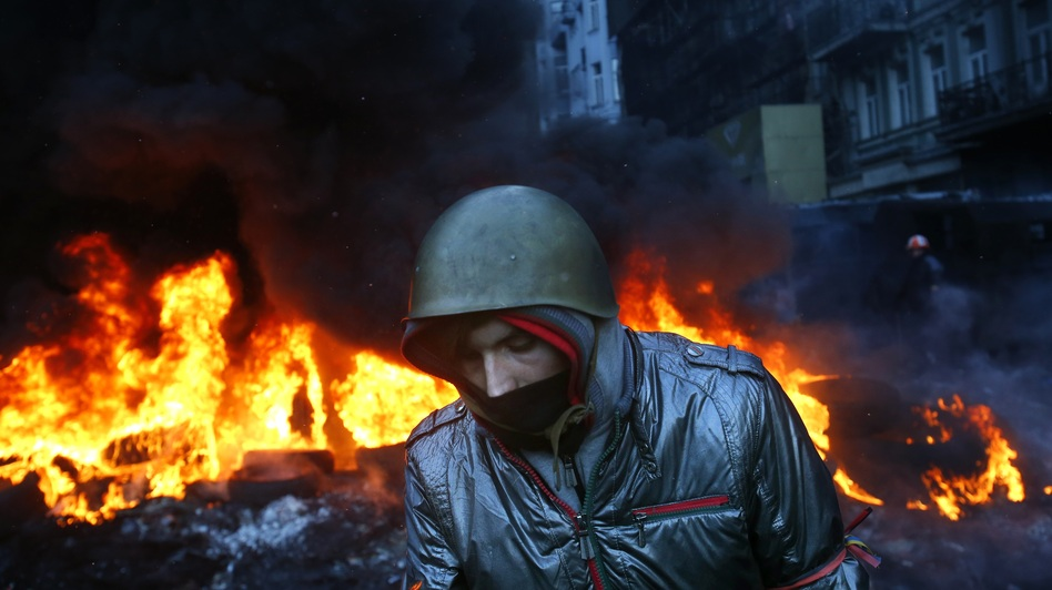 A protester walks pass burning tires in central Kiev, Ukraine, on Thursday. (AP)