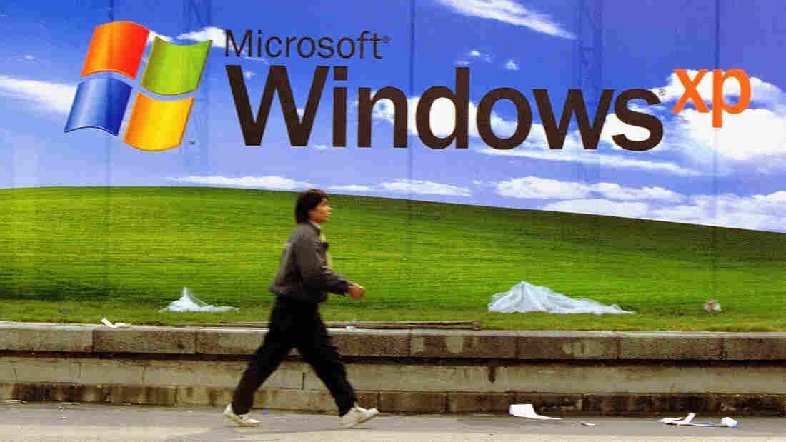 A man walks past a Microsoft billboard featuring Windows XP in November 2001 in Beijing.