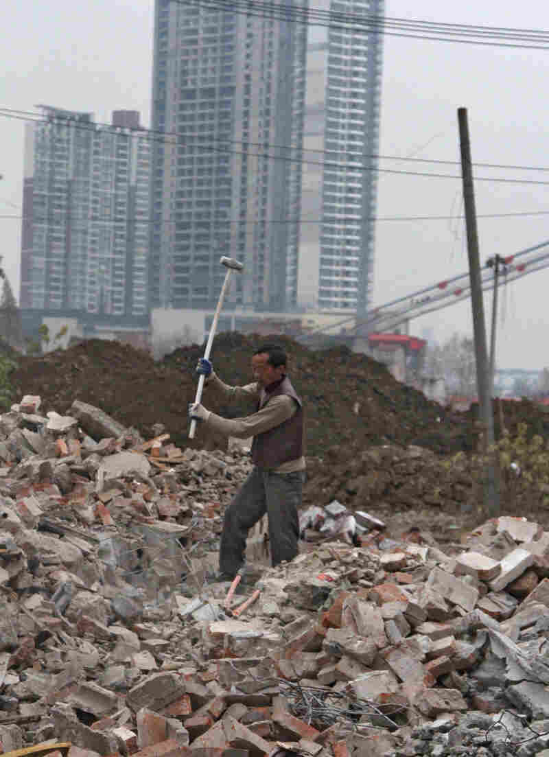 A scavenger pounds away at the rubble that was recently a neighborhood along the Yangtze River in Wuhan. The city is turning the area into a river drive.