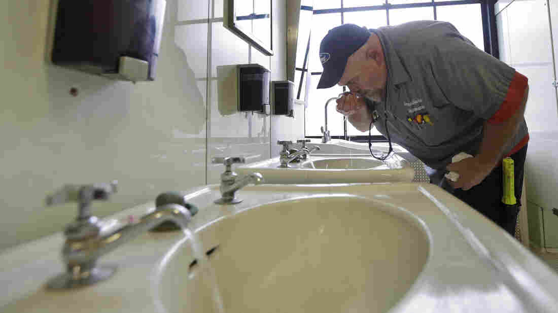 Al Jones of the West Virginia Department of General Services tests water as he flushes faucets and opens a rest room at the State Capitol in Charleston, W. Va., on Jan. 13, four days after a chemical spill into the Elk River. It wasn't until Jan. 21 that state officials were told by Freedom Industries that a second contaminant had also entered the river.