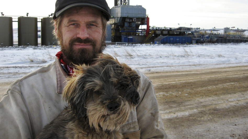 Donny Nelson with his dog Lucky. There are more than a dozen drilling rigs near his family's property. (NPR)