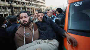 A man carries an Egyptian police officer to an ambulance af