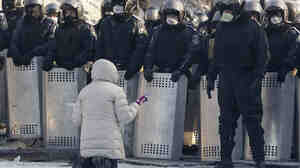On Friday in Kiev, a woman knelt as she appealed to Ukranian police troops at the site of clashes with anti-government protesters.
