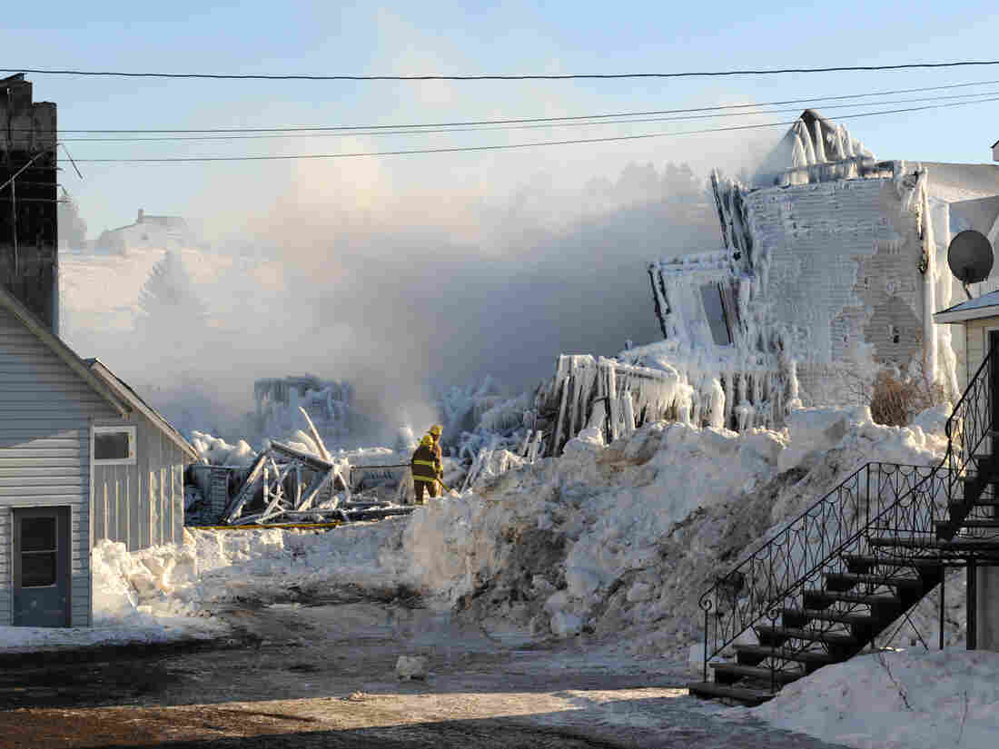 Smoke rises from the burned remains of a retirement home in L'Isle-Verte on Friday.