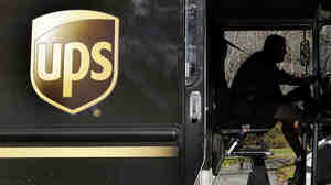 UPS has told workers that it will no longer offer health coverage for spouses who have their own job-based insurance. Above, a UPS driver makes a delivery in North Andover, Mass.