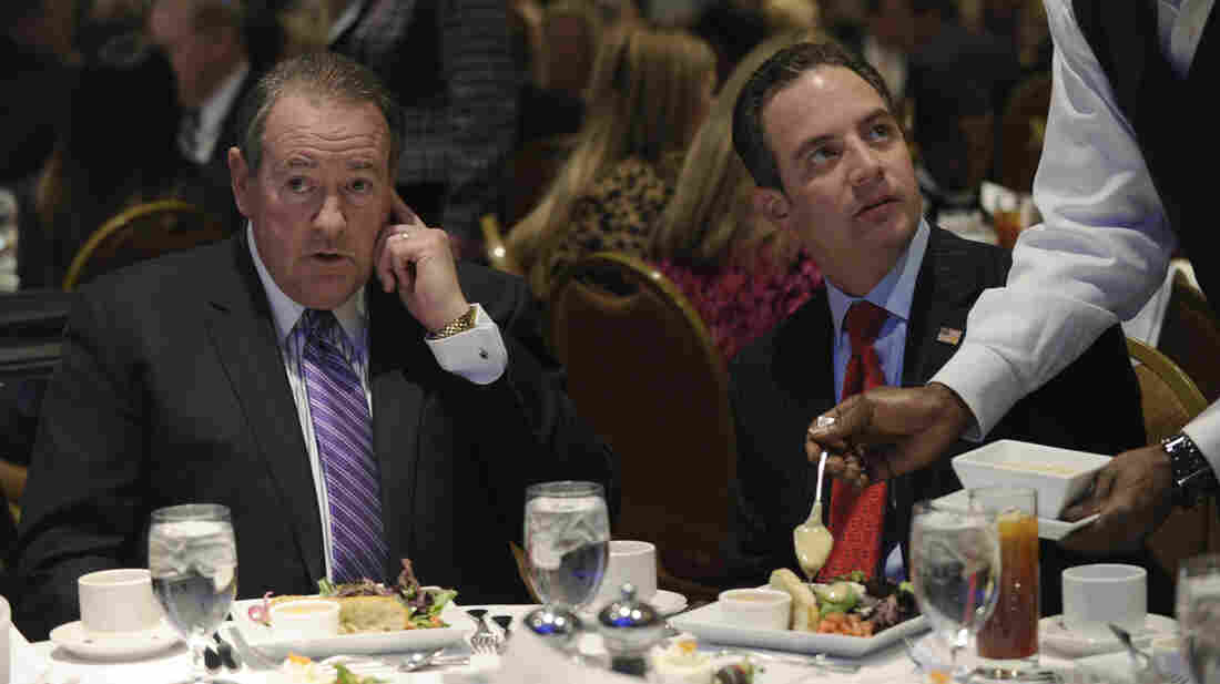 Mike Huckabee, left, sits with RNC Chairman Reince Priebus before Huckabee spoke at the Republican National Committee winter meeting in Washington on Thursday,