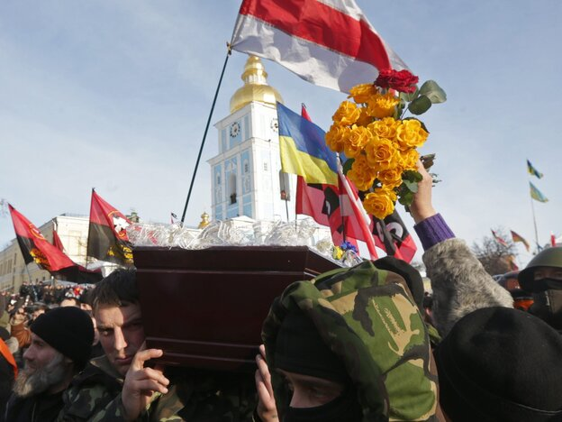 Ukrainian opposition activists on Sunday carry the coffin of their comrade Mikhail Zhiznevsky, killed during anti-government protests, in downtown Kiev, Ukraine.