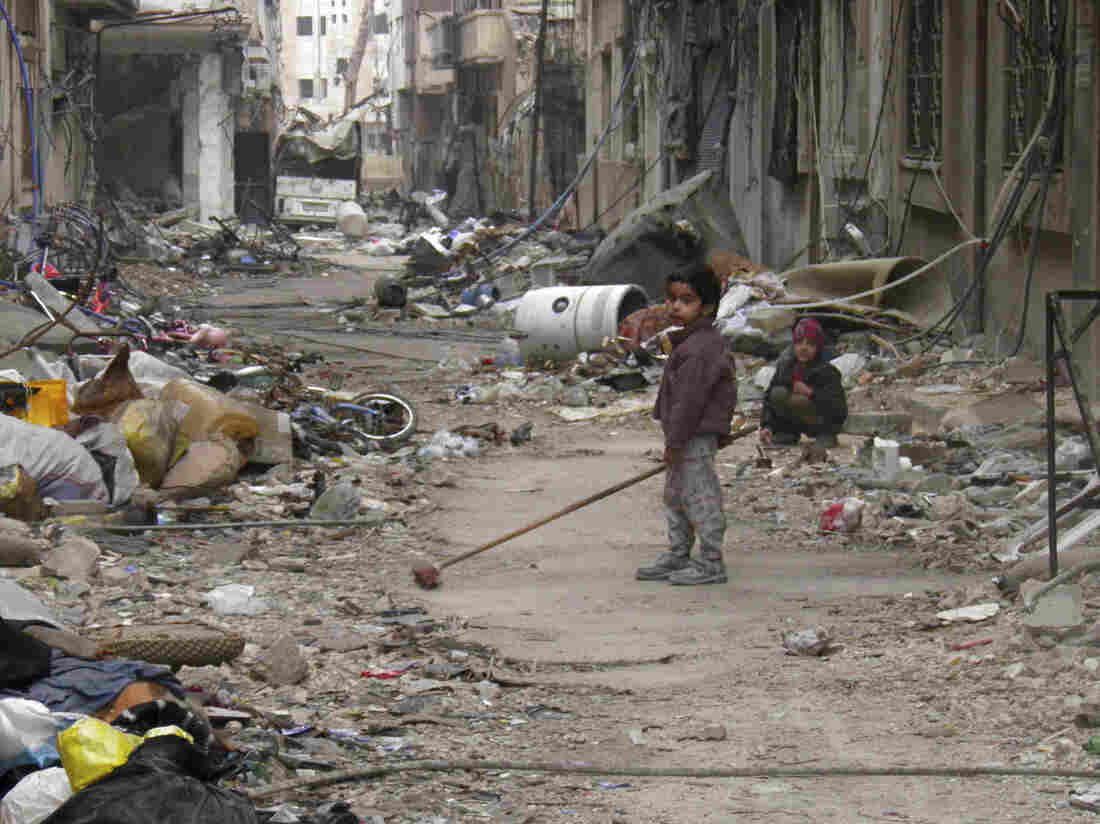 A child clears damage and debris in the besieged area of Homs on Sunday.