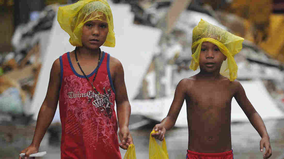 Young survivors of Typhoon Haiyan brave December rain as they ask for gifts from residents in the streets of Tacloban, Philippines. Months after the storm, cleanup is still ongoing and many of the more than 6,000 dead have yet to be identified.
