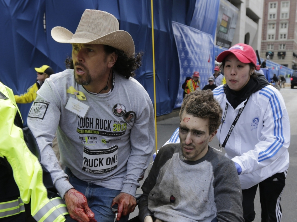An emergency responder and volunteers, including Carlos Arredondo, in the cowboy hat, push Jeff Bauman in a wheelchair after he was injured in one of two explosions near the finish line of the Boston Marathon. (Charles Krupa/AP)