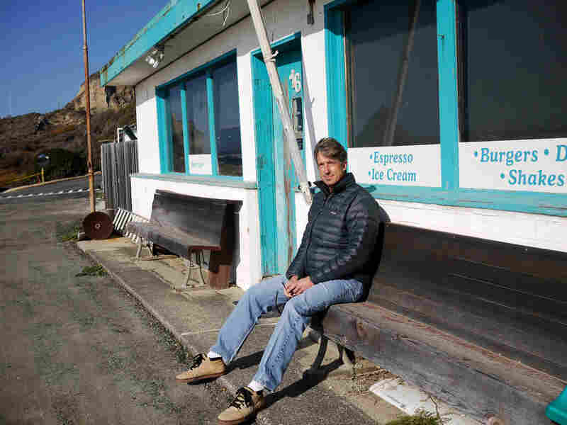 Mike Wallace, a high school surf coach, sits outside a cafe on Martins Beach. Some argue that amenities like the cafe, public bathrooms and a parking lot set a precedent of access.