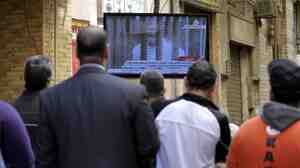 Egyptians watch a television screen showing the trial of ousted President Mohammed Morsi on Tuesday in Cairo.